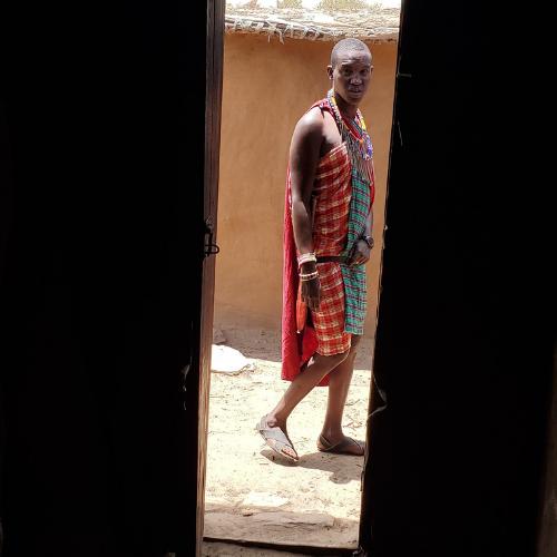 A Maasai warrior from inside a hut